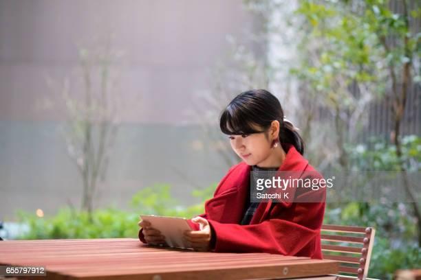 Jonge vrouw kijken scherm op digitale tablet bij terrasvormige ruimte