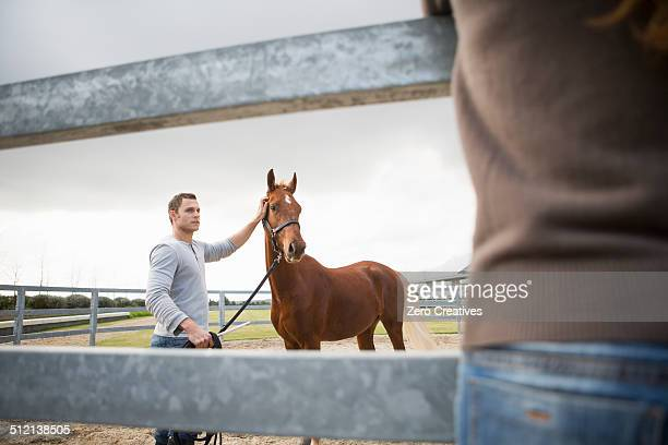 Young woman watching stablehand with horse in paddock ring