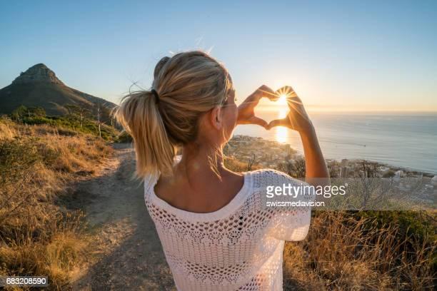 Junge Frau Sonnenuntergang am Meer macht Herzform