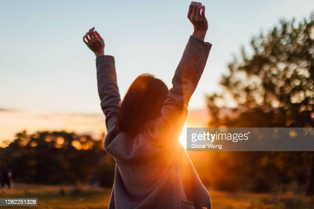 young woman watching sunset while enjoying nature - freedom stock pictures, royalty-free photos & images