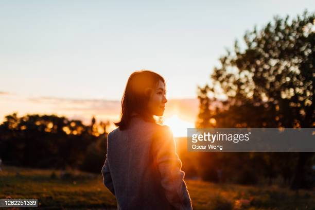 young woman watching sunset while enjoying nature - in silhouette stock pictures, royalty-free photos & images