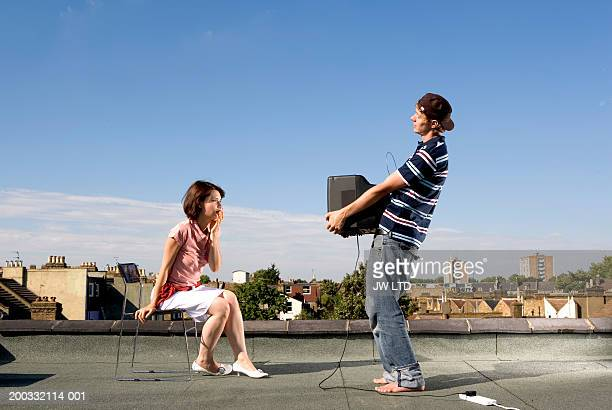 Young woman watching television held by young man on rooftop