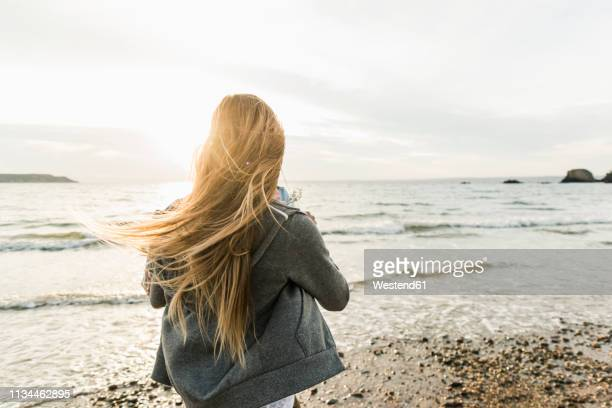 young woman watching the sunset on the beach - cheveux blonds photos et images de collection