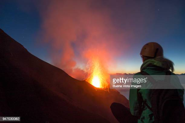 young woman watching volcanos' eruption - active volcano stock pictures, royalty-free photos & images
