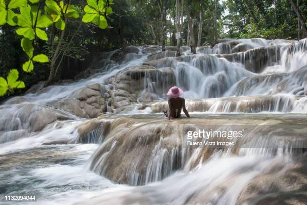 young woman watching waterfall - paisajes de jamaica fotografías e imágenes de stock