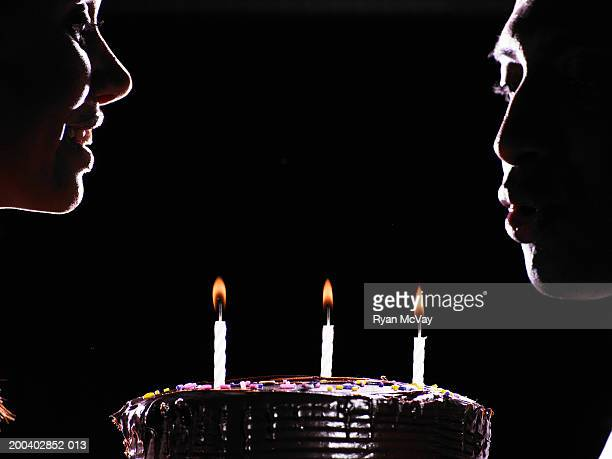 Young woman watching young man blow out candles on cake, side view