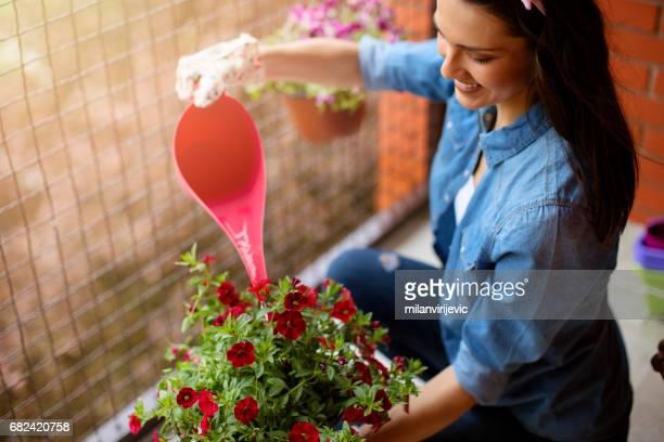 Junge Frau, die Bewässerung Blumen auf Terrasse
