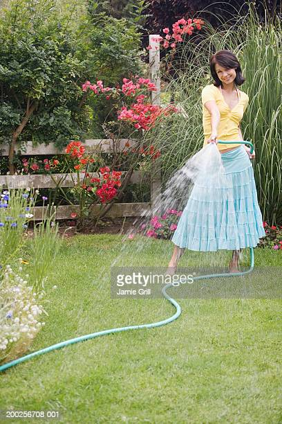 Young woman watering garden