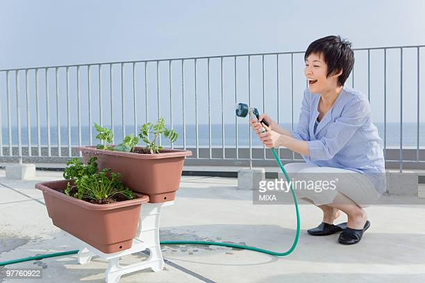 Young woman watering plant on veranda