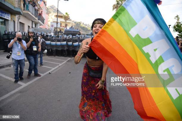 A young woman waves a Peace rainbow flag during a rally against the G7 Summit in GiardiniNaxos near the venue of the G7 summit of Heads of State and...