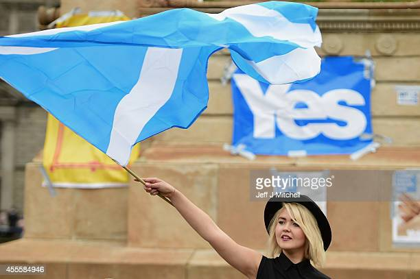 A young woman waves a Saltire flag as Yes activists gather in George Square on September 17 2014 in Glasgow ScotlandThe referendum debate has entered...