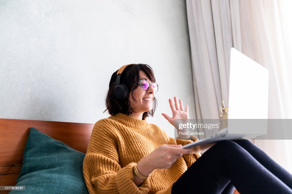 Young woman waves to colleagues on video conference meeting online : Stock Photo
