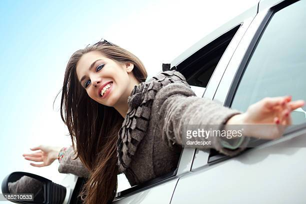 Young woman waving from car