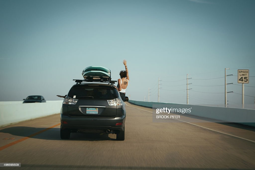 Young woman waving out SUV window : Stock Photo