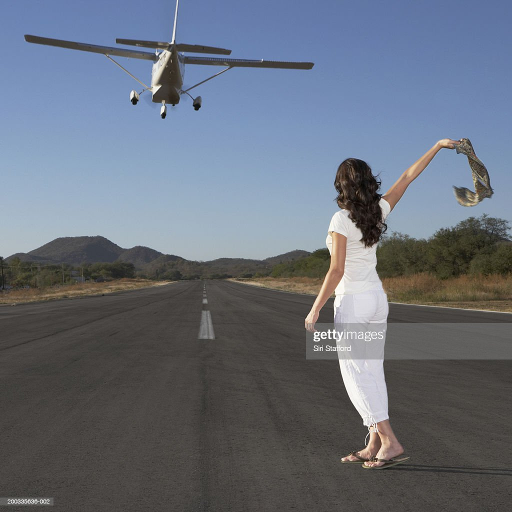 Young woman waving scarf to private plane in flight : Stock Photo