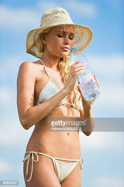 young woman wearing a bathsuit, holding a water bottle - drooping stock photos and pictures