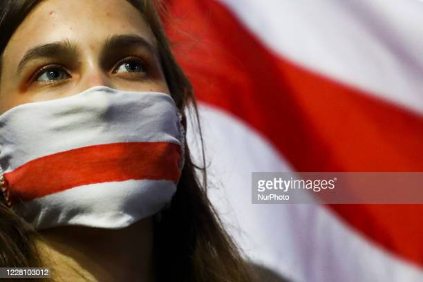 Young woman wearing a belarusian flag face mask demonstrates at the Main Square in solidarity with Belarus. Krakow, Poland on August 18, 2020....