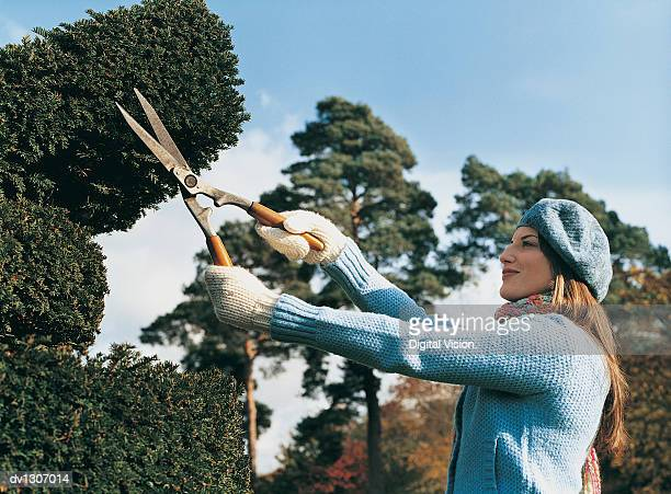 Young Woman Wearing a Beret Cutting a Hedge With Shears