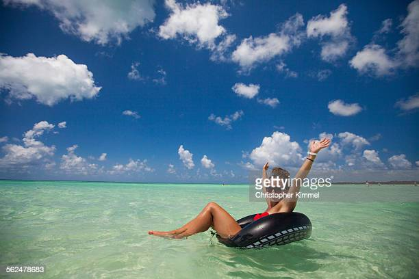 A young woman wearing a bikini floats on an inflatable tube in turquoise water while on vacation in Cayo Coco, Cuba.