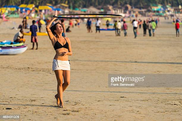 A young woman wearing a bikini is playing with a hoop at Palolem Beach with blue sky palm trees and white sand