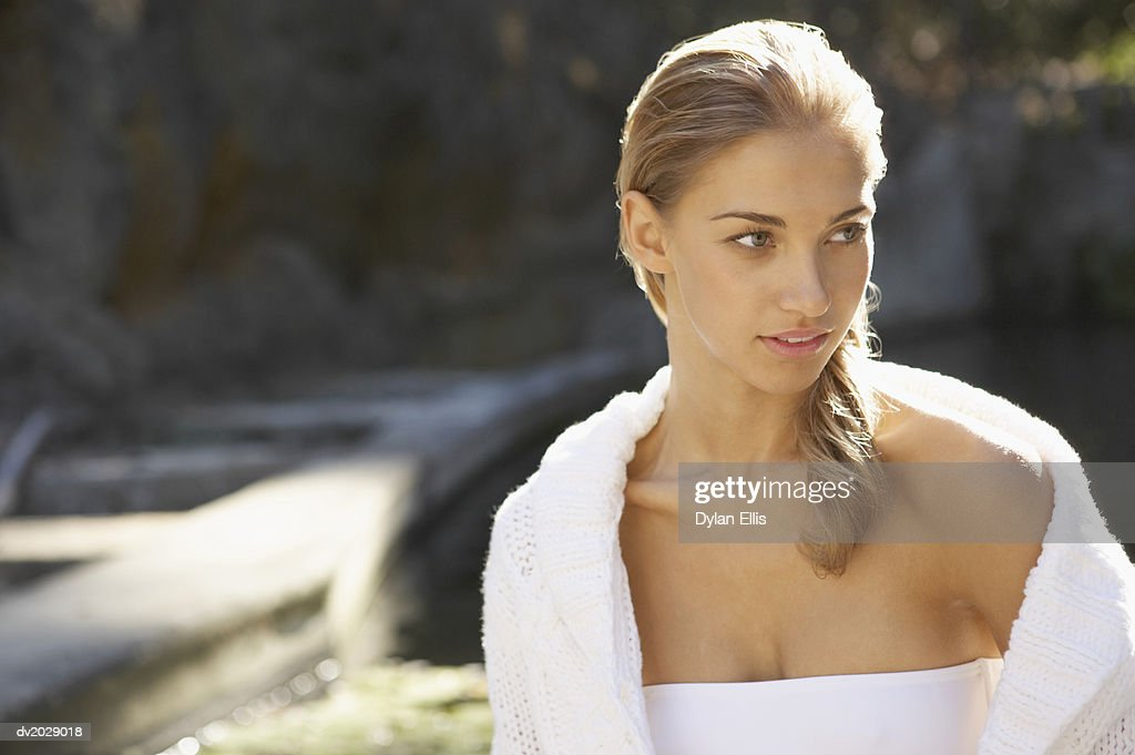 Young Woman Wearing a Bikini Top and a Cardigan Looking Sideways : Stock Photo
