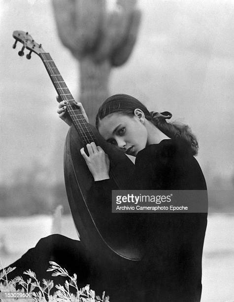 A young woman wearing a black dress and leaning on a lute circa 1948