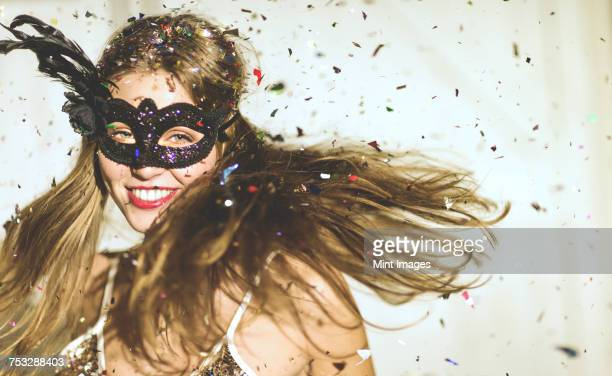 young woman wearing a black eye mask at a party with confetti falling. - black mask disguise stock pictures, royalty-free photos & images