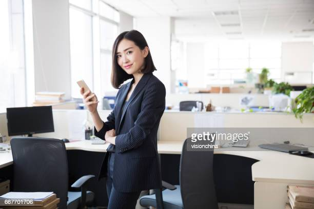young woman wearing a black suit,using the phone in the office - asia stock pictures, royalty-free photos & images