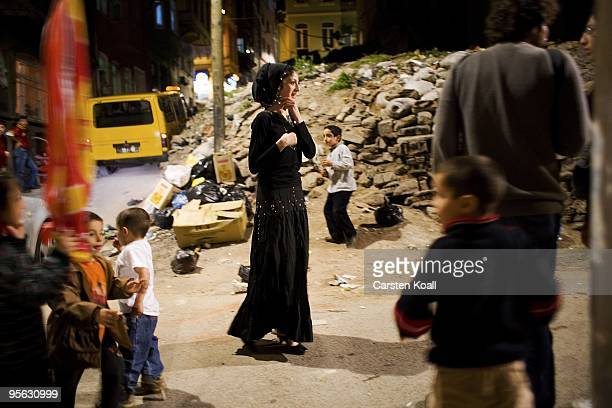 Young woman wearing a black traditional roma dress and childs enjoy a wedding party in the district Tarlabasi on May 14, 2006 in Istanbul, Turkey....