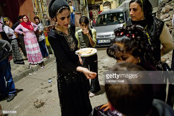 Young woman wearing a black traditional roma dress shares out sweets for the guests at a wedding party in the district Tarlabasi on May 14, 2006 in...