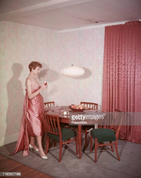 A young woman wearing a cherry blossom pink evening gown standing next to a dining table and chairs in the dining room of a house in England in June...
