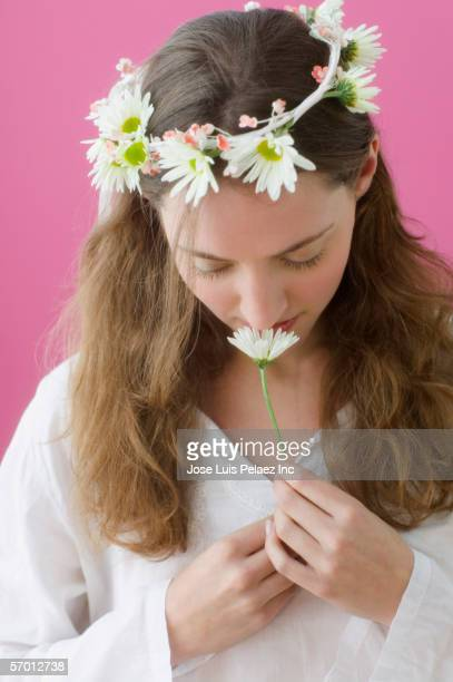 Young woman wearing a daisy crown and smelling a flower