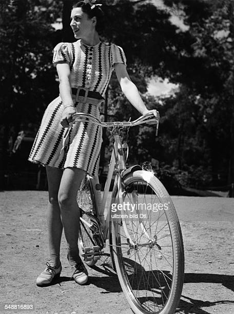 Young woman wearing a dress for riding bicycle um 1938 Photographer Gyula H Brassai Published by 'Berliner Illustrirte Zeitung' 27/1938 Vintage...