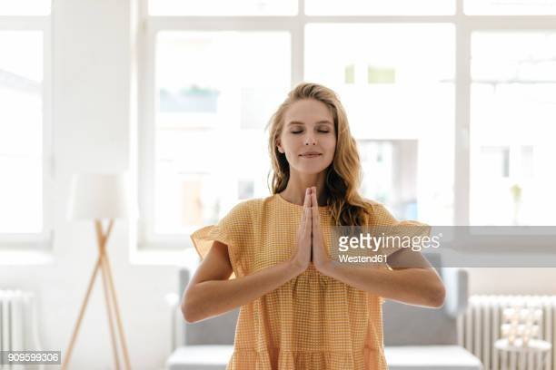 young woman wearing a dress practising yoga - wohlbefinden stock-fotos und bilder