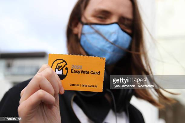 Young woman wearing a face mask holds up her Easy Vote card on the way to vote on the first day of advance voting in the 2020 General Election on 3...