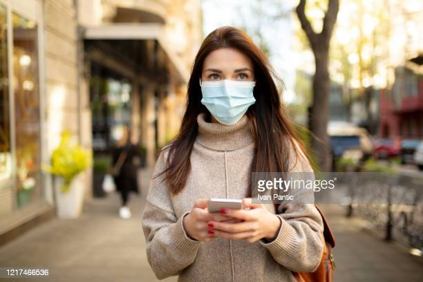 young woman wearing a face mask - n95 respirator mask stock pictures, royalty-free photos & images