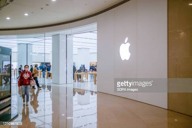 A young woman wearing a face mask walking by Apple store's main entrance Apple launched sales of its latest iPhone SE around the world