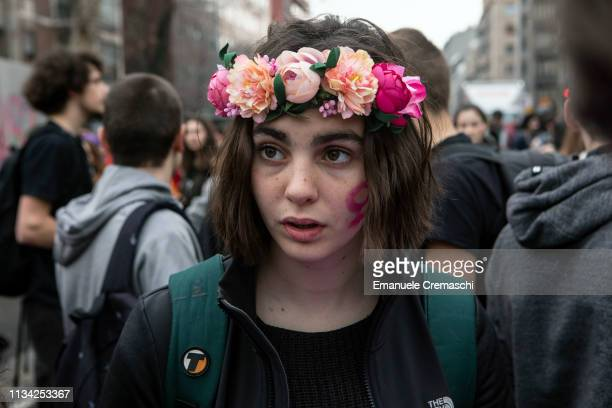 A young woman wearing a flowers crown looks on while she takes part to a student demonstration against gender violence and calling for gender parity...