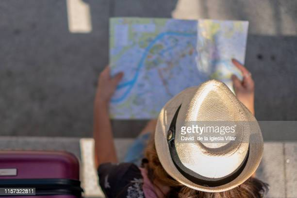 young woman wearing a hat consulting a map - estrada da vida imagens e fotografias de stock