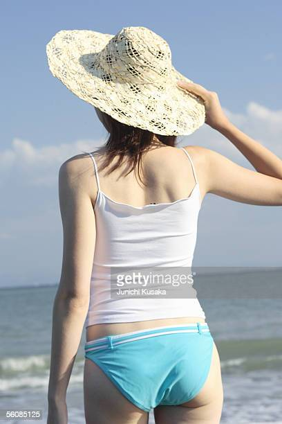 A young woman wearing a hat in beach, rear view