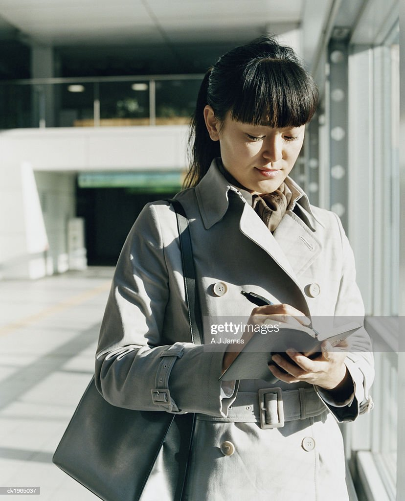 Young Woman Wearing a Mackintosh Raincoat and Writing in a Personal Organizer : Stock Photo