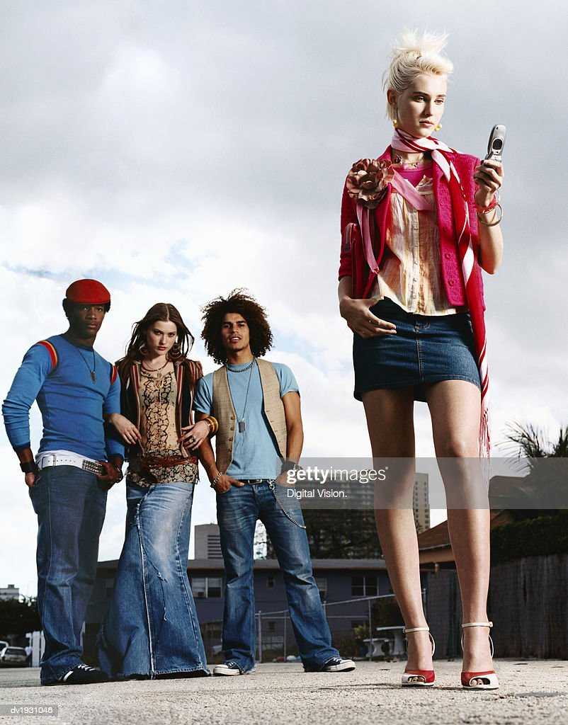 Young Woman Wearing a Mini Skirt and Using a Mobile Phone and Men and Women Wearing Jeans, Out in a City Street : Stock Photo