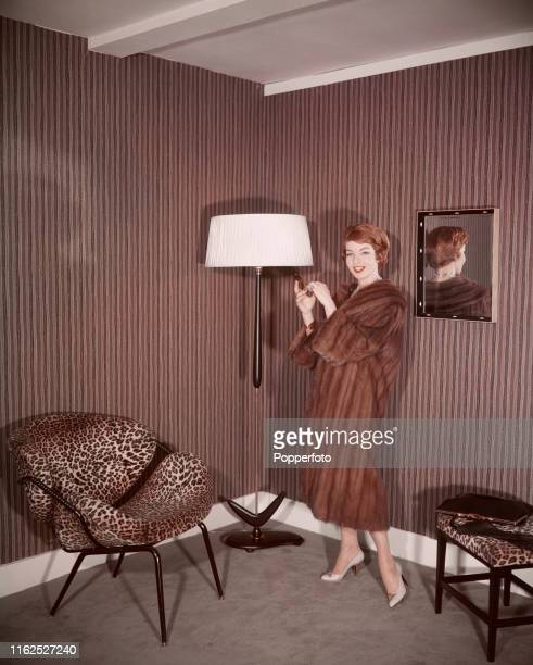 A young woman wearing a mink coat standing next to an upright lamp leopard spot lounge chair and matching stool in the living room of a house in...
