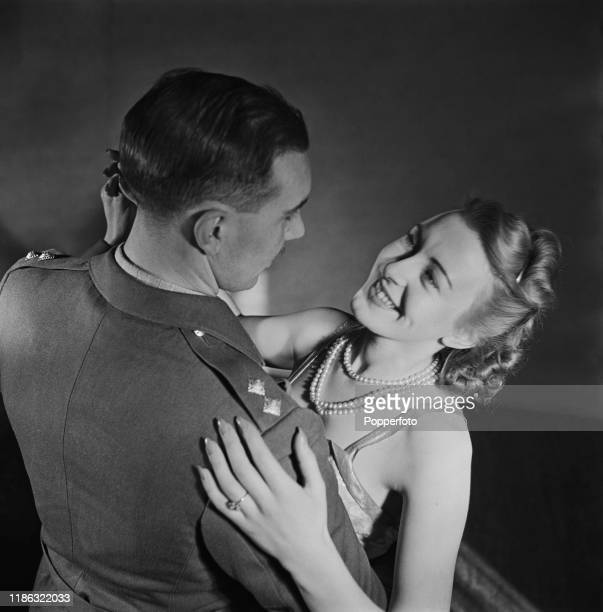 A young woman wearing a pearl necklace dances with a man wearing military uniform at a society dance in England during World War II 16th January 1940
