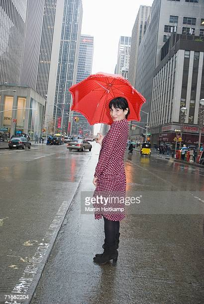 Young woman wearing a polka dot dress and holding a red umbrella in city street, New York City