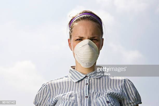 A young woman wearing a pollution mask