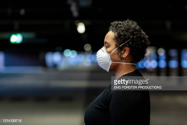 young woman wearing a protective face mask to prevent the spread of virus in the city - パンデミック ストックフォトと画像