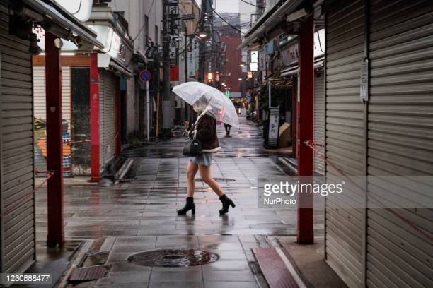 Young woman wearing a protective face mask walks with an umbrella at the deserted street in Tokyo, Japan on 28 January, 2021.