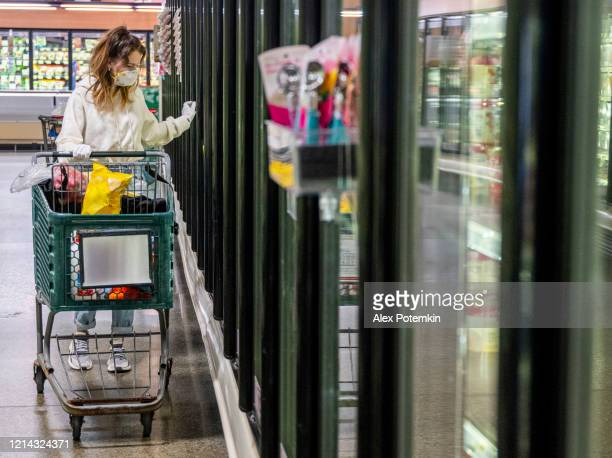 a young woman wearing a protective mask and gloves shopping in a time of virus pandemic, buying food supplies - processed frozen foods. - panic buying stock pictures, royalty-free photos & images