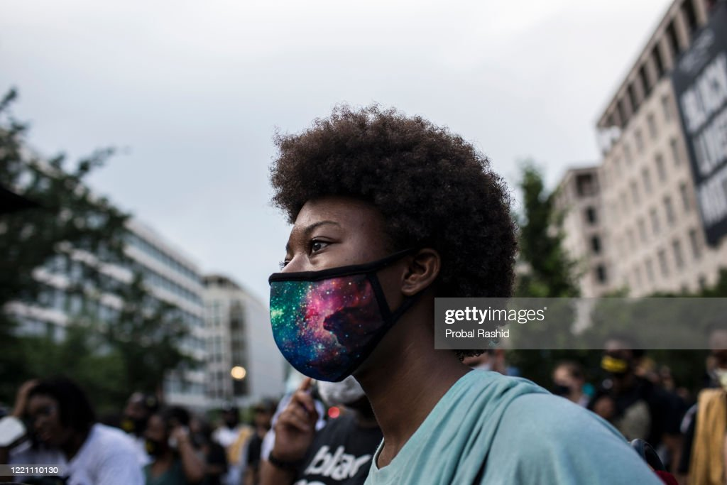A young woman wearing a protective mask at a gathering to... : News Photo